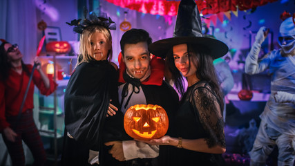 Halloween Costume Party: Father Count Dracula Holds Little Bat Girl Daughter and Hugs Witch Wife for a Happy Family Portrait. In the Background Monsters Having Fun