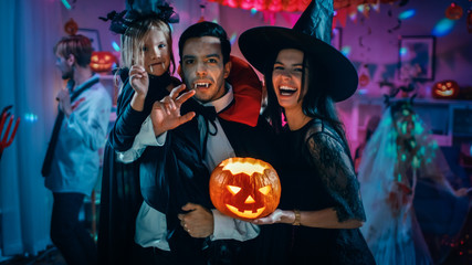 Halloween Costume Party: Father Count Dracula Holds Little Bat Girl Daughter and Hugs Witch Wife for a Happy Family Portrait. In the Background Monsters Having Fun Wall mural