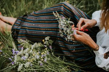 Folk girl in the midsummer making flower