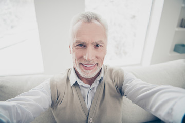 Close up photo amazing macho he him his aged man make take selfies friendly positive modern white perfect ideal teeth wear white shirt waistcoat pants cozy divan flat house living room indoors