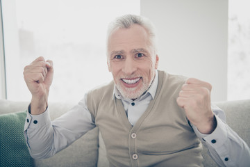 Close up photo amazing funky he him his aged man observe athletic match game achievement arms hands raised air wear white shirt waistcoat pants sit comfort bright flat house living room indoors