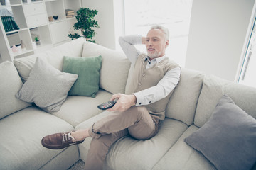 Close up side profile photo amazing funky he him his aged man arms hands console change tv channel media wear specs white shirt waistcoat pants sit comfort bright flat house living room indoors
