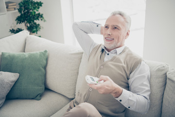 Close up photo amazing he him his aged man arms hands behind head console change mode system turn on cooling regime wear white shirt waistcoat pants sit comfy bright flat house living room indoors