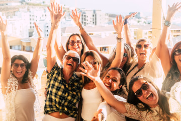 Happy and cheerful group of women friends together dancing and having fun on the rooftop at home - people celebrating together with laughing a lot and enjoying friendship - city view background Wall mural