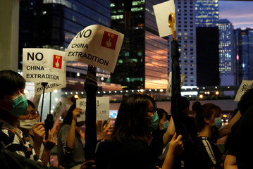 People hold placards during a protest following a day of violence over a proposed extradition bill, near the Legislative Council building in Hong Kong