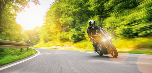 motorbike on the forest road riding fast. having fun driving on the empty road. Wall mural