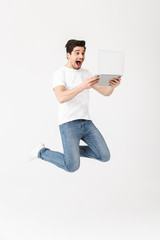 Happy excited young man posing isolated over white wall using laptop computer jumping.