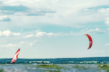 Kitesurfer and windsurfer sailing past each other. A variety of outdoor activities on water concept Wall mural