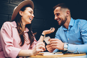 Cheerful male and female friends enjoying free time together joking and share multimedia in networks during meeting in cafe, romantic couple laughing viewing funny photos on mobile phone during date