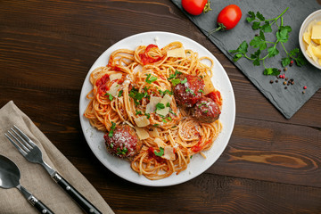 Delicious spaghetti pasta with meatballs and tomato sauce on a plate. Traditional American Italian food on a rustic wooden table. Top view shot directly above.