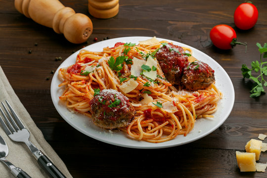 Delicious spaghetti pasta with meatballs and tomato sauce on a plate. Traditional American Italian food on a rustic wooden table.