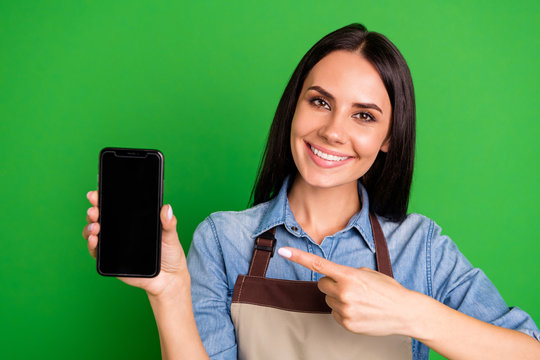Close up photo beautiful she her lady hands arms telephone indicate finger customer buy buyer advising best offer sales prices wear jeans denim shirt covered work apron isolated black grey background