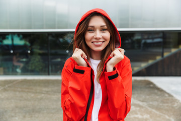 Beautiful excited emotional young happy pretty woman in raincoat posing outdoors.