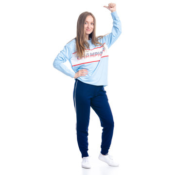 Woman in blue sweatpants sport style casual standing looking smiling showing pointing on white background isolation