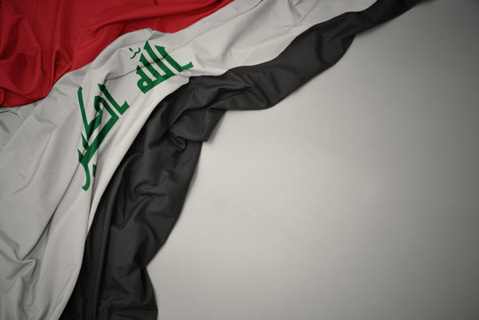 waving national flag of iraq on a gray background.