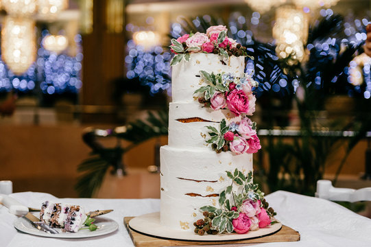 Three-tiered wedding cake with white mastic and peonies isolated