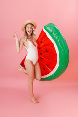 Excited young woman posing isolated over pink wall background dressed in swimwear beach concept with air mattress watermelon.