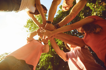 Friends hold hands in the park in the summer. Wall mural