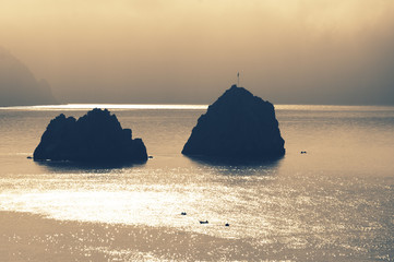 Two rocks and fisher boats in sea at sunrise