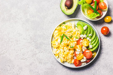 Scrambled eggs with cherry tomatoes , avocado feta cheese and olive oil. Top view, space for text.