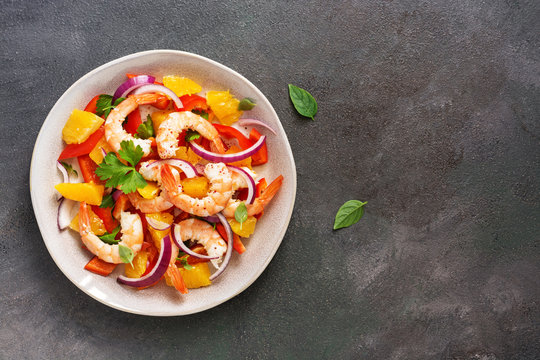 Ceviche salad with shrimps and oranges on a dark rustic background. Latin American food. Top view, flat lay, copy space.