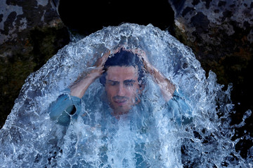 A man cools off under a water pipe from a canal on the outskirts of Peshawar
