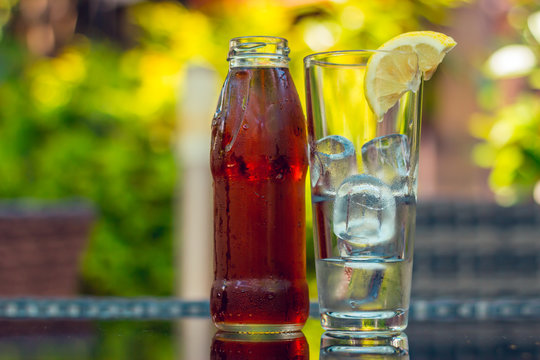 Bottle full of sweet brown ice tea and glass with ice cubes and a half slice of lemon sitting next to it on a colorful background – Cold beverage served at bars and restaurants during summertime