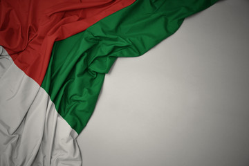 waving national flag of madagascar on a gray background.