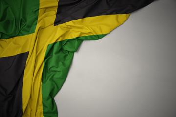 Papiers peints Amérique du Sud waving national flag of jamaica on a gray background.