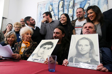 Javier Matias Darroux Mijalchuk, son of Elena Mijalchuk and Juan Manuel Darroux, who disappeared during Argentina's former 1976-1983 dictatorship, holds an image of his father, during a news conference in Buenos Aires