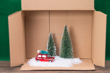 Scale car with trees and snow in a box