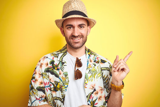 Young man on vacation wearing hawaiian flowers shirt and summer hat over yellow background with a big smile on face, pointing with hand and finger to the side looking at the camera.