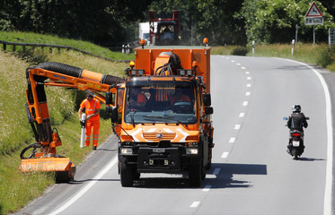 Workers drive a Mercedes Benz Unimog truck with a mower arm to cut the grass verve beside a road near Landquart