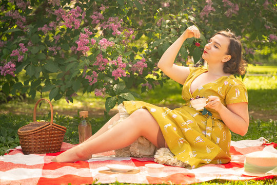 cute plus size caucasian girl wearing a cute vintage yellow dress and enjoying a vacation in the summer Park on the green grass. curvy pinup woman in retro dress has rest on the nature near the lilac