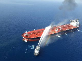 An Iranian navy boat tries to stop the fire of an oil tanker after it was attacked in the Gulf of Oman