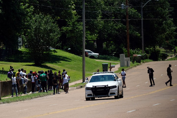 A police car drives by a group of people the day after violent clashes between police and protesters broke out on streets overnight in Memphis