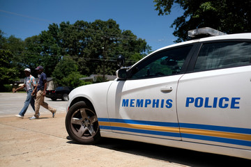 Two men walk in front of a police car the day after violent clashes between police and protesters broke out on streets overnight in Frayser