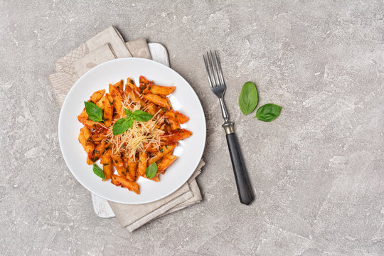 Penne pasta in tomato sauce with parmesan cheese and basil