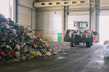 Tractor transports garbage at the plant for processing and sorting waste. Raised bulldozer bucket with waste. Pile of trash in the garbage factory hangar