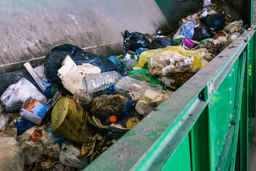 Waste container on the sorting line of a recycling plant. The process of separating garbage in a container. Packages, iron cans and plastic bottles
