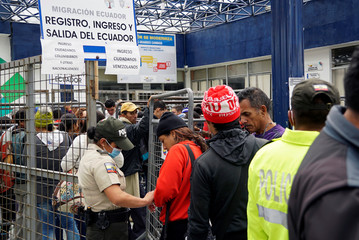 Ecuadorian police check documents from Venezuelans as they are crossing into Ecuador from Colombia, some to reach Peru ahead of a June 15 deadline of new migration laws, at the Rumichaca International Bridge in Tulcan