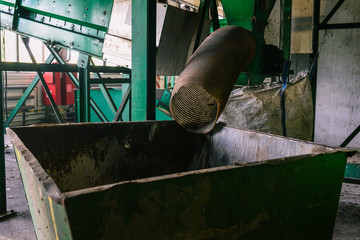 Large green container for waste collection. The pipe from which the garbage comes. Sorting and recycling