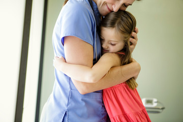 Young girl hugs doctor