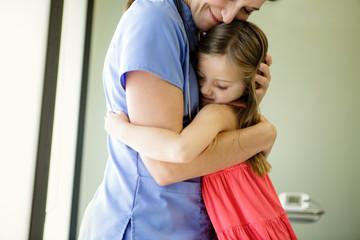 Young girl hugs woman doctor