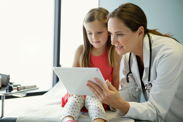 Woman doctor shows tablet to young patient
