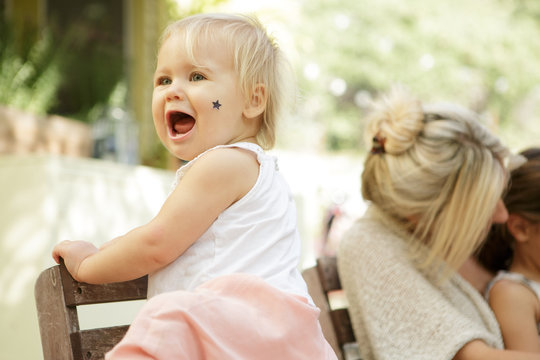 Blonde toddler yelling with sticker on her cheek