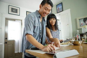 Couple cooking together with digital recipe on tablet