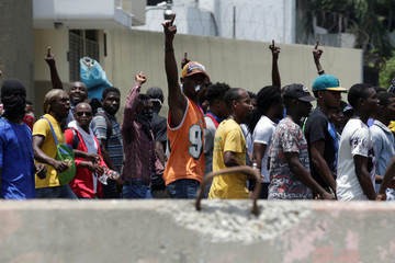 Protesters gesture in front of the police during a demonstration against the government of President Jovenel Moise in the streets of Port-au-Prince