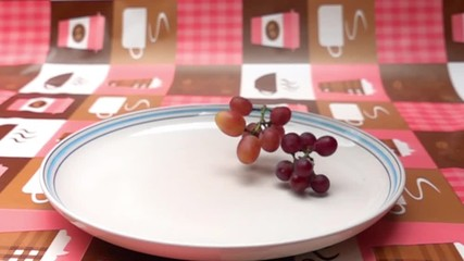 Fototapete - Bunches of grapes fall into a white plate on the table in Slow Motion