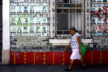 A woman walks in front of a wall with images of people disappeared during the Guatemala civil war ahead of Sunday's presidential election in Guatemala City